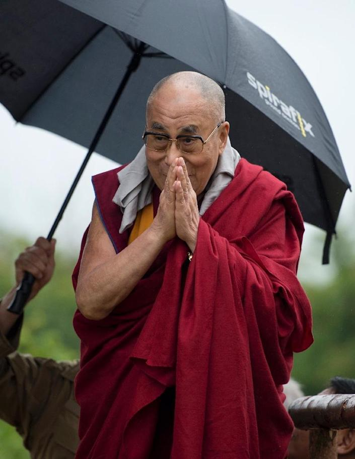 The Dalai Lama arrives to address an audience near the Stone Circle as he visits the Glastonbury Festival of Music and Performing Arts on Worthy Farm near the village of Pilton in Somerset, South West England on June 28, 2015 (AFP Photo/Oli Scarff)