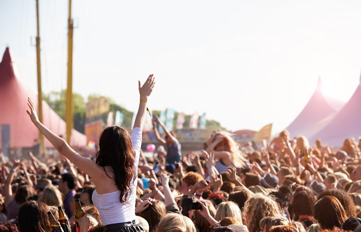 Crowds Enjoying Themselves At Outdoor Music Festival With Arms in The Air