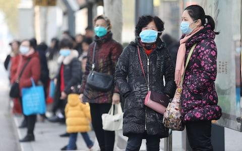 Locals in Wuhan are wearing masks to protect themselves - Credit: REX