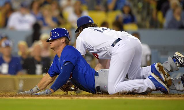 Chicago Cubs' Ryan Sweeney, left, scores on a wild pitch as Los Angeles Dodgers starting pitcher Dan Haren falls over him after missing the throw from A.J. Ellis during the third inning of a baseball game, Friday, Aug. 1, 2014, in Los Angeles. (AP Photo/Mark J. Terrill)