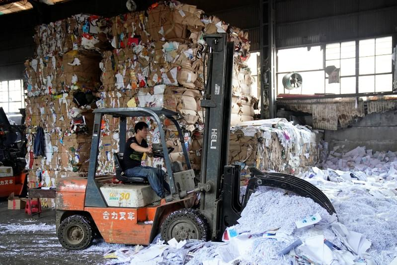 A laborer works at a paper products recycling station in Shanghai