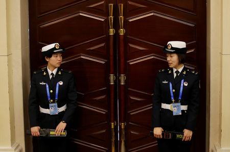 Female soldiers of the People's Liberation Army (PLA) Navy stand at an entrance during a news conference ahead of the 70th anniversary of the founding of Chinese People's Liberation Army Navy, in Qingdao, China, April 20, 2019. REUTERS/Jason Lee
