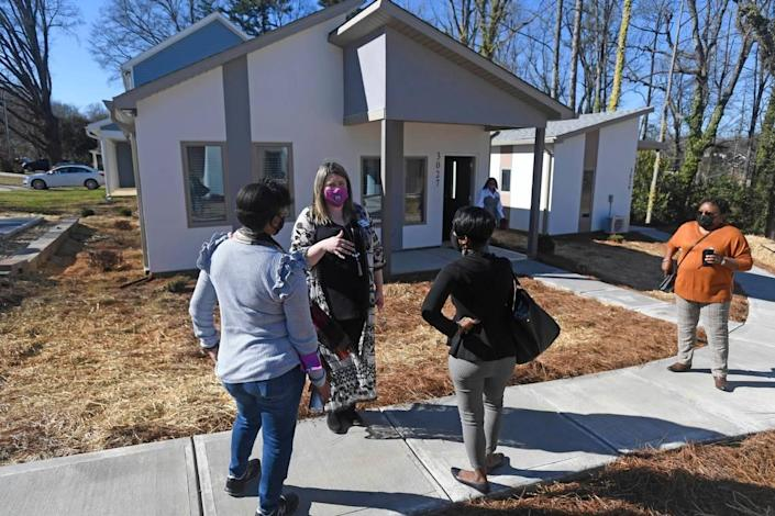 Rachel Cody, Director of Marketing for Home Again Foundation, center, talks about the cottages during the opening of the new affordable housing community, launched by the nonprofit in Charlotte on Wednesday, February 24, 2021. The group has built 8 single family units with energy efficient affordable units with goals of expansion with further fundraising. The program will have additional services to help people improve their financial stability.