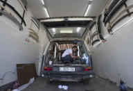 A welder converts a van into a food truck, at a workshop in the West Bank city of Ramallah, Tuesday, Sept. 22, 2020. With dine-in restaurants mostly closed due to health restrictions, food trucks have allowed entrepreneurial Palestinian businessmen to find a way to keep working. (AP Photo/Nasser Nasser)