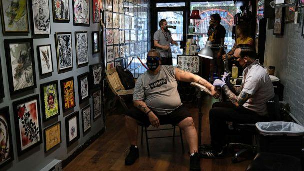 PHOTO: Artist Jeremy Miller gives Jay Rivera a tattoo at New York Hardcore Tattoos on the first day of re-opening as New York City officially begins Phase Three of opening on July 06, 2020, in New York. (Spencer Platt/Getty Images)