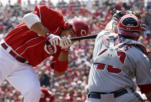 Cincinnati Reds' Joey Votto falls off the plate after being hit in the hands by a pitch from Washington Nationals starting pitcher Ross Detwiler in the first inning of a baseball game, Saturday, April 6, 2013, in Cincinnati. Nationals catcher Wilson Ramos catches the pitch at right. (AP Photo/Al Behrman)