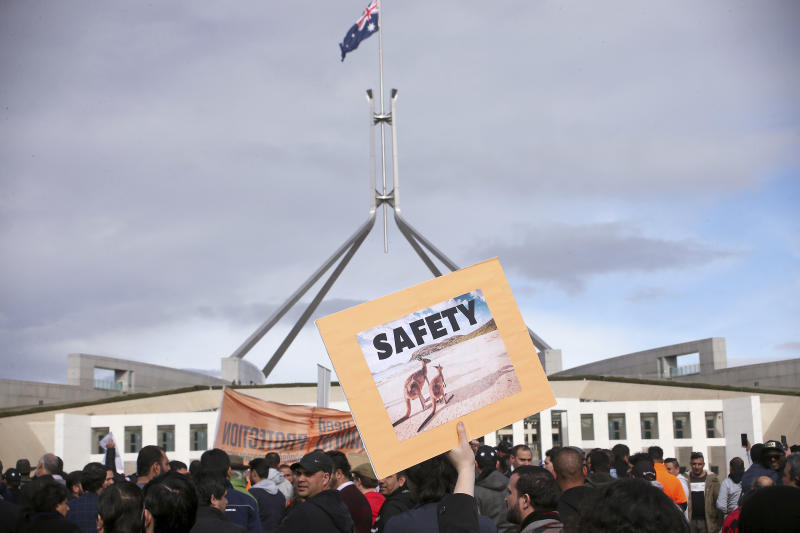 A protestor holds up a placard adorned with kangaroos during a refugee protest at Parliament House in Canberra, Australia, Monday, July 29, 2019. Hundreds of protesters are rallying outside Parliament House highlighting the uncertain futures of many refugees since Australia replaced permanent protection visas with temporary visas. (AP Photo/Rod McGuirk)