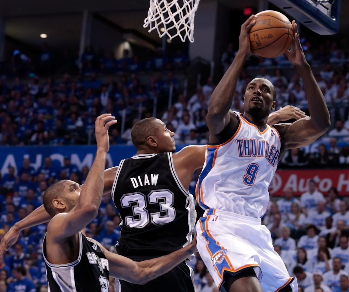 OKLAHOMA CITY, OK - JUNE 02:  Serge Ibaka #9 of the Oklahoma City Thunder goes up for a shot against Tim Duncan #21 and Boris Diaw #33 of the San Antonio Spurs in the first quarter in Game Four of the Western Conference Finals of the 2012 NBA Playoffs at Chesapeake Energy Arena on June 2, 2012 in Oklahoma City, Oklahoma. NOTE TO USER: User expressly acknowledges and agrees that, by downloading and or using this photograph, User is consenting to the terms and conditions of the Getty Images License Agreement.  (Photo by Brett Deering/Getty Images)