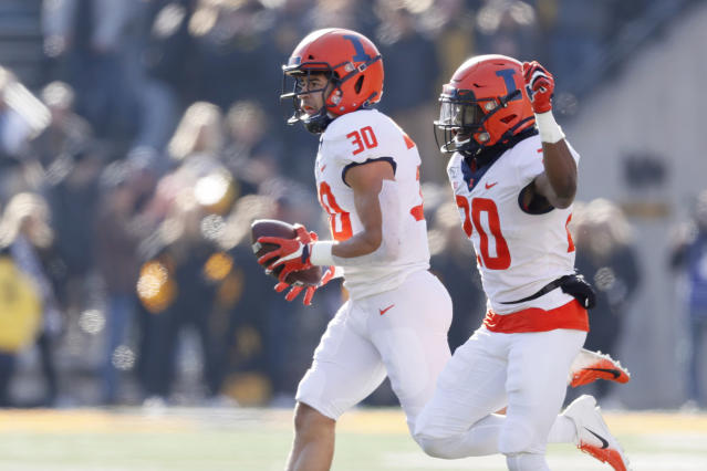 Illinois defensive back Sydney Brown (30) celebrates with teammate Nick Walker, right, after intercepting a pass during the first half of an NCAA college football game against Iowa, Saturday, Nov. 23, 2019, in Iowa City, Iowa. (AP Photo/Charlie Neibergall)
