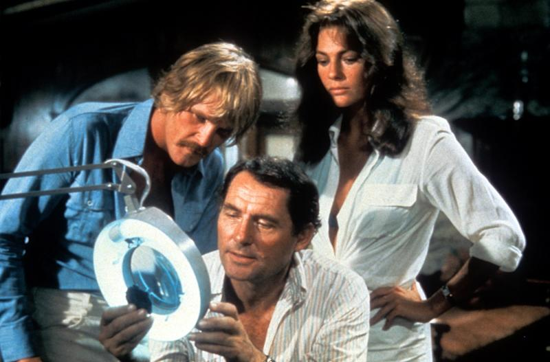 Nick Nolte, Robert Shaw, and Jacqueline Bisset looking at object under lit microscope in a scene from the film 'The Deep', 1977. (Photo by Columbia Pictures/Getty Images)