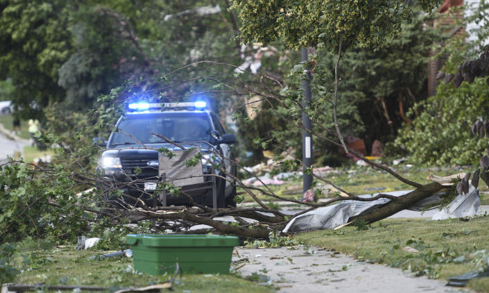 Trees block roads and sidewalks after an overnight tornado touched down in Naperville, Ill. A radar-confirmed tornado swept through communities in heavily populated suburban Chicago, damaging more than 100 homes, toppling trees, knocking out power and causing multiple injuries, officials said, Monday, June 21, 2021. (Paul Valade/Daily Herald via AP)