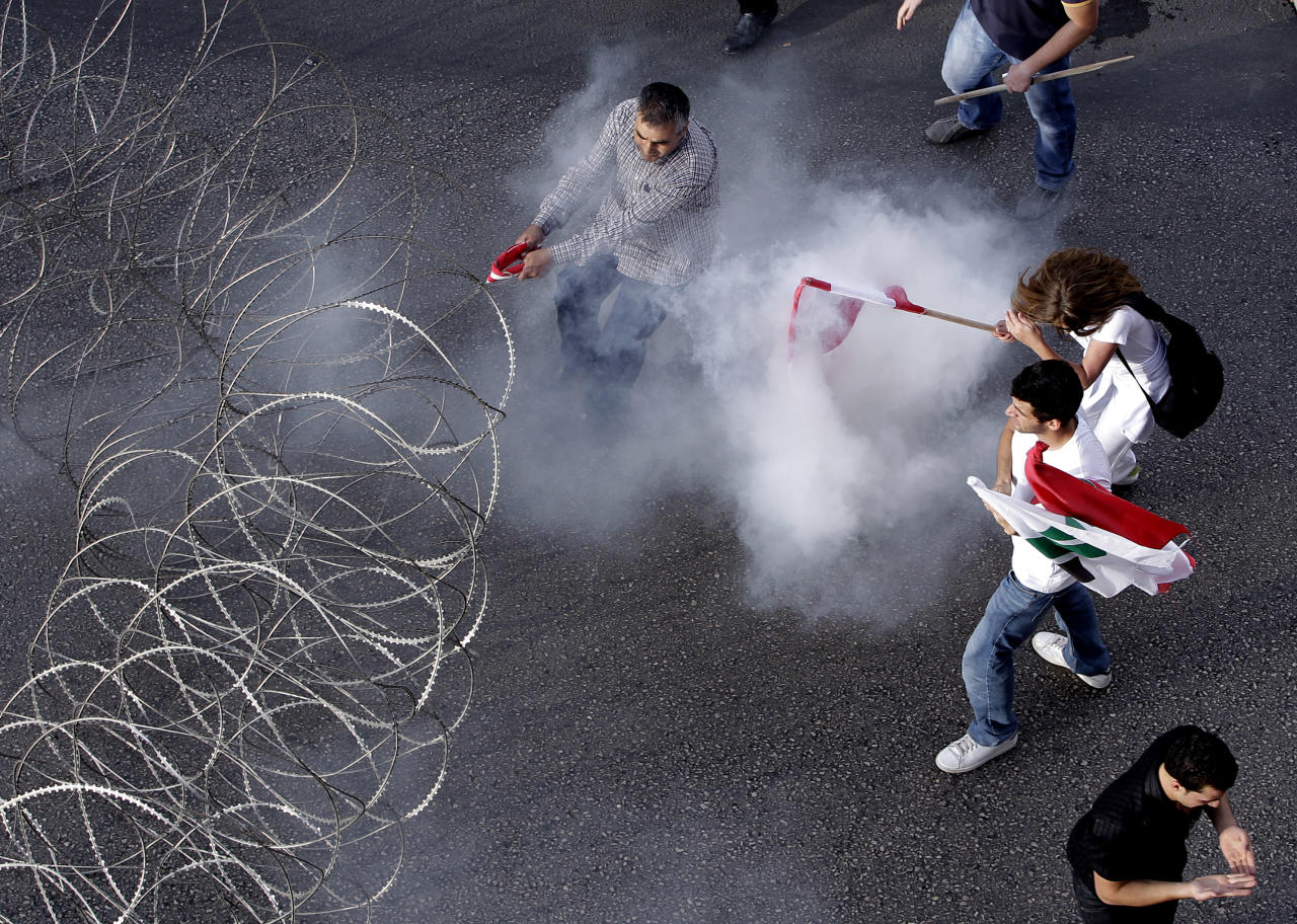 Lebanese protesters are enveloped in tear gas as they pull a barbed-wire barrier during clashes after the funeral of Brig. Gen. Wissam al-Hassan who was assassinated on Friday by a car bomb in Beirut, Lebanon, Sunday Oct. 21, 2012. Lebanese soldiers fired guns and tear gas to push back hundreds of protesters who broke through a police cordon and tried to storm the government headquarters in Beirut. The enraged crowd came from the funeral of a top Lebanese intelligence official assassinated in a massive car bombing.(AP Photo/Hussein Malla)
