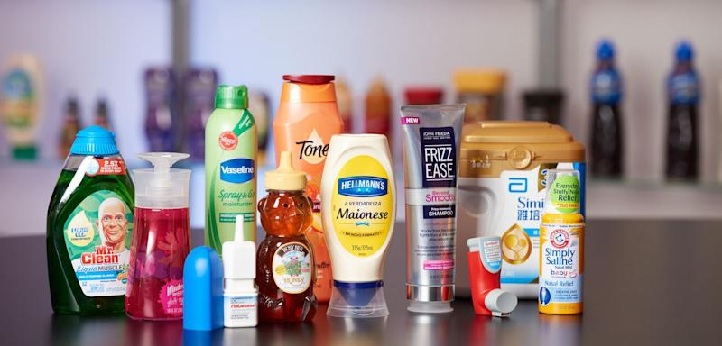 Various plastic containers from AptarGroup with products including soap, honey, mayonnaise, and eye drops.
