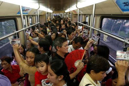 FILE PHOTO: Commuters ride a train during rush hour on Southeast Asia's first light rail transit network, which is 29-years-old, in Manila