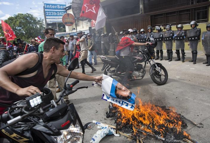 "A man burns a photo of President Juan Orlando Hernández during a protest in Tegucigalpa, Honduras. <span class=""copyright"">(Rodrigo Abd / Associated Press)</span>"