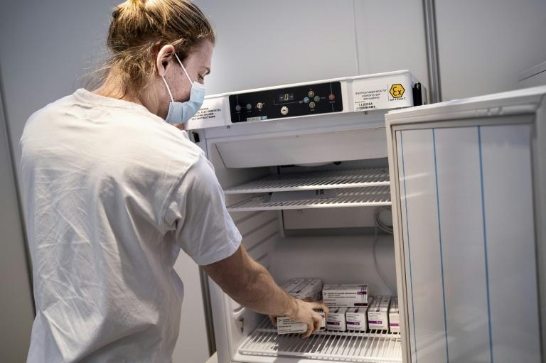 A medical staffer takes AstraZeneca vaccines out of the freezer at an inoculation center in Copenhagen