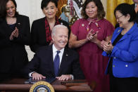 President Joe Biden smiles after signing the COVID-19 Hate Crimes Act, in the East Room of the White House, Thursday, May 20, 2021, in Washington. Top row from left, Vice President Kamala Harris, Rep. Judy Chu, D-Calif., Rep. Grace Meng, D-N.Y., and Sen. Mazie Hirono, D-Hawaii. (AP Photo/Evan Vucci)
