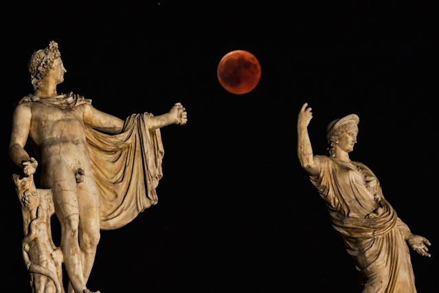 "<p>A picture shows the full moon during a ""blood moon"" eclipse beside a statue of ancient Greek goddess Hera (R) and god Apollo in central Athens on July 27, 2018. (Photo: Aris Messinis/AFP/Getty Images) </p>"