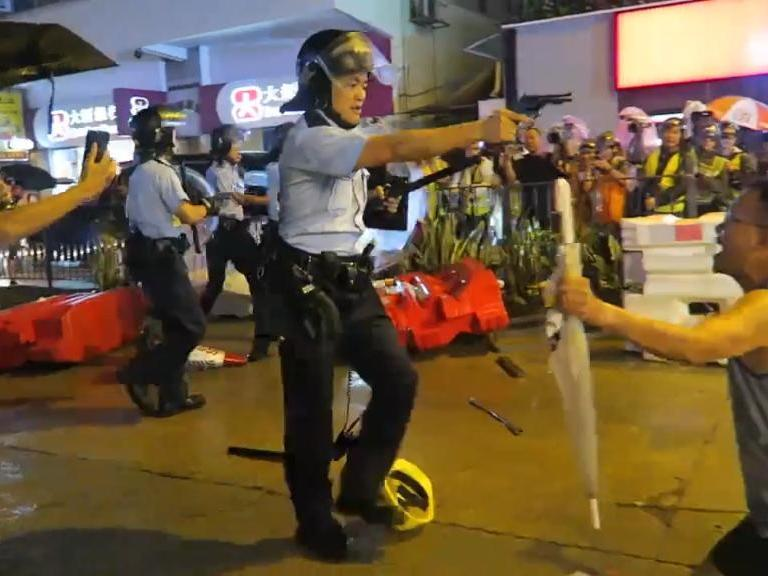 Video has emerged (grab, pictured) showing police officers pointing guns at the crowd in a bid to scare them: SocREC