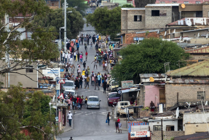 Residents of the densely populated Alexandra township east of Johannesburg gather in the streets Friday, March 27, 2020. South Africa went into a nationwide lockdown for 21 days in an effort to mitigate the spread to the coronavirus, but in Alexandra, many people were gathering in the streets disregarding the lockdown. The new coronavirus causes mild or moderate symptoms for most people, but for some, especially older adults and people with existing health problems, it can cause more severe illness or death.(AP Photo/Jerome Delay)