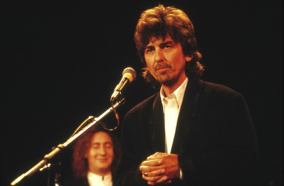 George Harrison with Julian Lennon behind, at The Beatles' induction to the Rock & Roll Hall Of Fame (Photo by Ebet Roberts/Redferns)