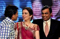 "Reliance Industries Chairman Mukesh Ambani (R) and wife Nita (C) interact with Indian cricketer Sachin Tendulkar (L) during the Reliance Foundation's ""Real Heroes Awards"" ceremony in Mumbai on March 24, 2012. AFP PHOTO/STR"