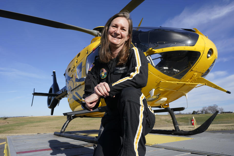 Air ambulance flight paramedic, Rita Krenz, poses in front of her company's helicopter in Weyers Cave, Va., Monday, March 15, 2021. Krenz started a fund-raising campaign that brought in more than $18,000 for the charity that has helped RIP Medical Debt forgive the debt of more than 900 people so far. (AP Photo/Steve Helber)