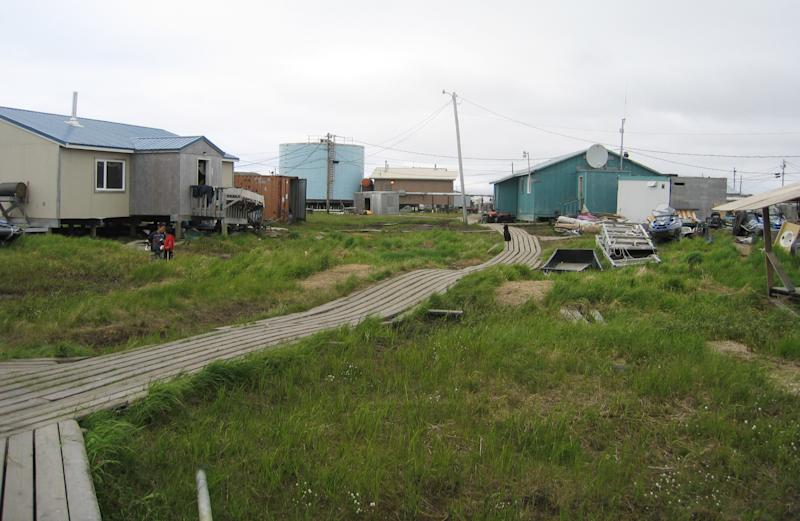 In this 2006 photo provided by the State of Alaska Department of Commerce, wooden boards connect houses in Newtok, Alaska. The flood-prone village of Newtok near Alaska's storm-battered coast is running out of time as coastal erosion creeps ever closer to the Yup'ik Eskimo community. As residents wait for a new village to be built on higher ground nine miles away, a dispute over who is in charge has led to a rare intervention by the Bureau of Indian Affairs, which ruled that the sitting tribal council no longer represents the community of 350 as far as the agency is concerned. (AP Photo/State of Alaska)