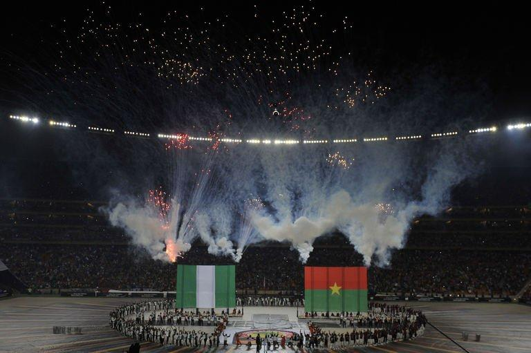 Artists perform around giant Nigerian and Burkina Faso flags on February 10, 2013 at Soccer City stadium