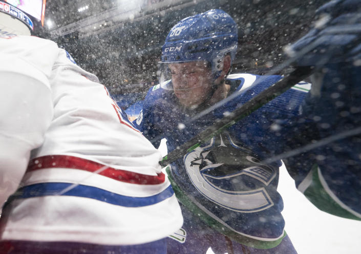 Vancouver Canucks defenseman Nate Schmidt (88) puts Montreal Canadiens right wing Brendan Gallagher (11) into the boards during the first period of an NHL hockey game Wednesday, Jan. 20, 2021, in Vancouver, British Columbia. (Jonathan Hayward/The Canadian Press via AP)
