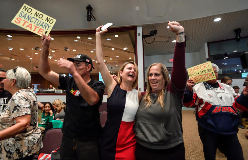 FILE - In this March 27, 2018, file photo, David Hernandez, left, Genevieve Peters, center, and Jennifer Martinez celebrate after the Orange County Board of Supervisors voted to join the U.S. Department of Justice lawsuit against the State of California's sanctuary cities law (SB54) during their meeting in Santa Ana, Calif. More local governments in California are resisting the state's efforts to resist the Trump administration's immigration crackdown, and political experts see politics at play as Republicans try to fire up voters in a state where the GOP has grown weak. (Jeff Gritchen/The Orange County Register via AP, File)