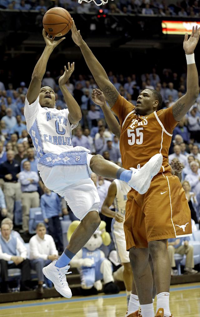 Texas' Cameron Ridley (55) defends as North Carolina's Nate Britt (0) drives to the basket during the first half of an NCAA college basketball game in Chapel Hill, N.C., Wednesday, Dec. 18, 2013. (AP Photo/Gerry Broome)
