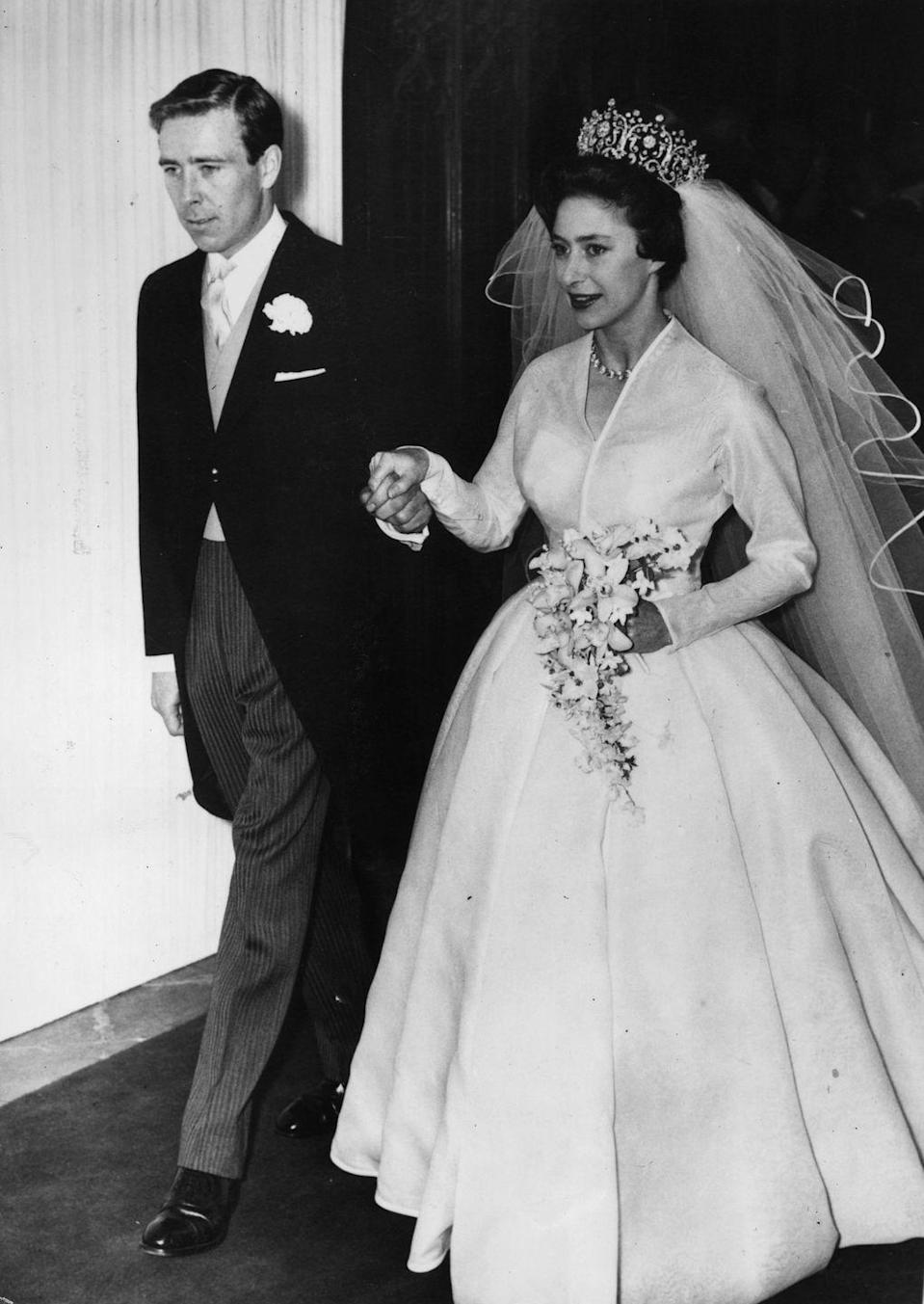 <p>The Queen's younger sister wore a long-sleeve silk organza wedding dress designed by Norman Hartnell when she married Antony Armstrong-Jones. The Princess paired the simple dress with the Poltimore tiara and a cathedral length veil. </p>