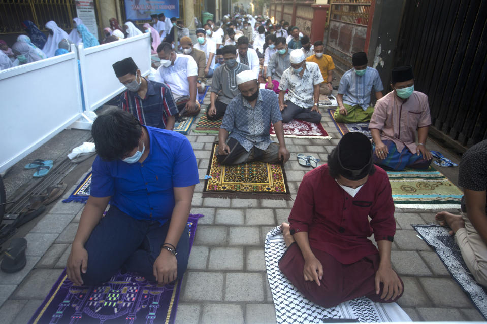Muslims wearing face masks offer the Eid al-Fitr prayer with a distance setting in Bali, Indonesia on Thursday, May 13, 2021. Indonesian Muslims perform Eid al-Fitr prayer that marks the end of the holy fasting month of Ramadan. (AP Photo/Firdia Lisnawati)