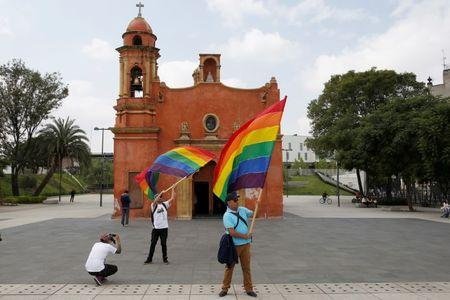 Participants wave a rainbow flag in front of a church during a march in support of gay marriage, sexual and gender diversity in Mexico City, Mexico