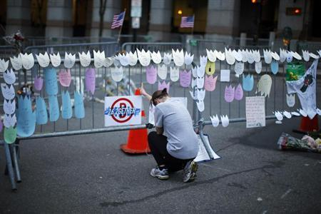 A woman kneels and cries in front of a memorial to the Boston Marathon bombings victims, at the barricades surrounding the scene in Boston