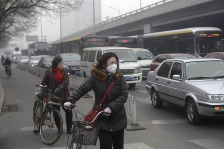 File photo of a woman wearing a mask stands besides her bicycle as vehicles stop at a traffic junction on a busy street amid thick haze in Beijing