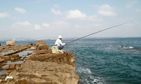 Fisherman dangles his line to catch fish in the island of Arwad