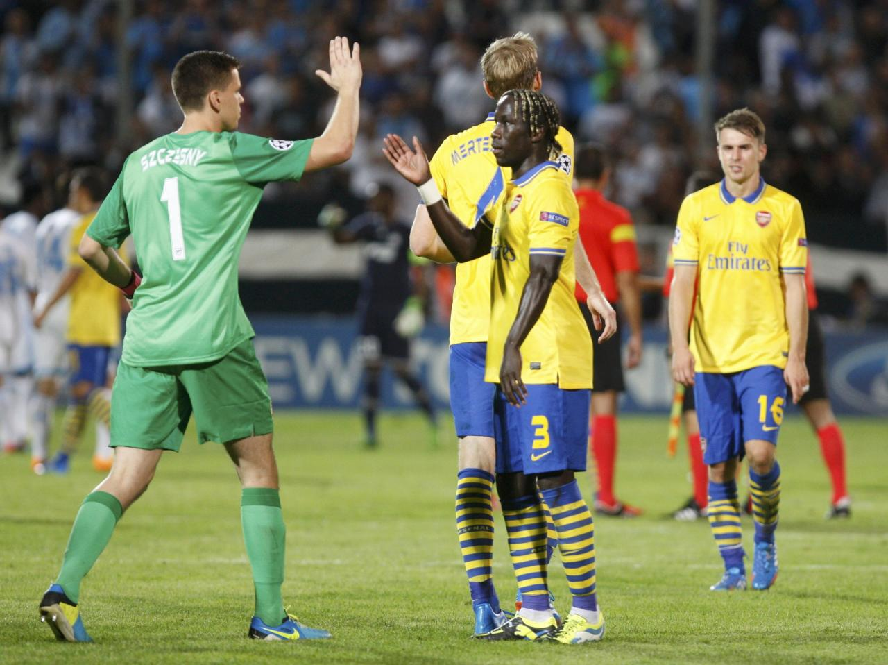 Arsenal's Wojciech Szczesny and Bacary Sagna (R) celebrate after their team won their Group F Champions League soccer match against Olympique Marseille at the Velodrome stadium in Marseille, September 18, 2013. REUTERS/Philippe Laurenson (FRANCE - Tags: SPORT SOCCER)