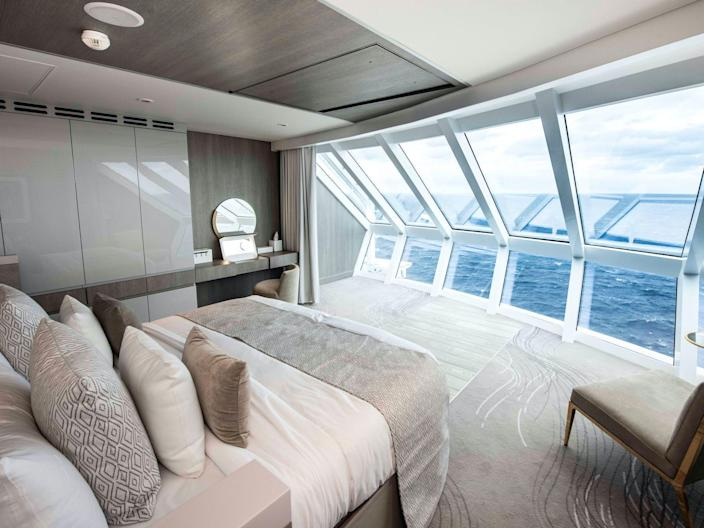 a bed, desk, and chair overlooking the ocean in the Iconic Suite of the Celebrity Edge