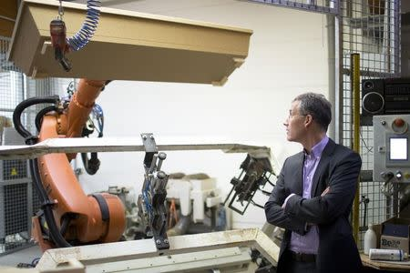 Coffin maker Michael Jagdt (CEO of lignotech Massivholz GmbH) watches a robot arm moving a coffin in Berlin, December 1, 2014. REUTERS/Axel Schmidt