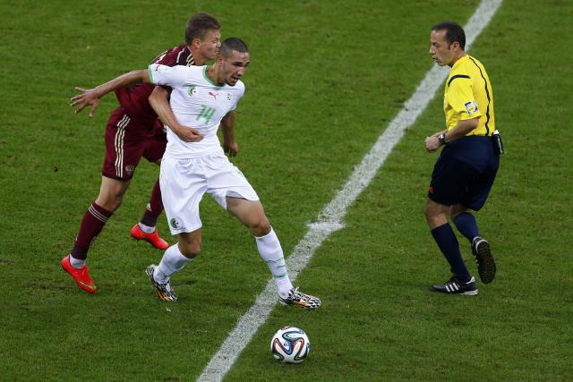 Russia's Oleg Shatov (L) fights for the ball with Algeria's Nabil Bentaleb during their 2014 World Cup Group H soccer match at the Baixada arena in Curitiba June 26, 2014. REUTERS/Amr Abdallah Dalsh (BRAZIL - Tags: SOCCER SPORT WORLD CUP)