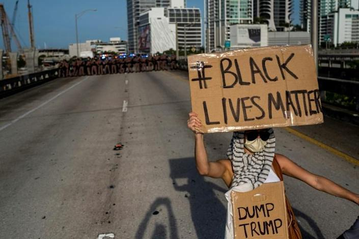 A protestor holding a Black Lives Matter / Dump Trump sign stands in front of a Florida state trooper line during a rally in Miami (AFP Photo/Ricardo ARDUENGO)