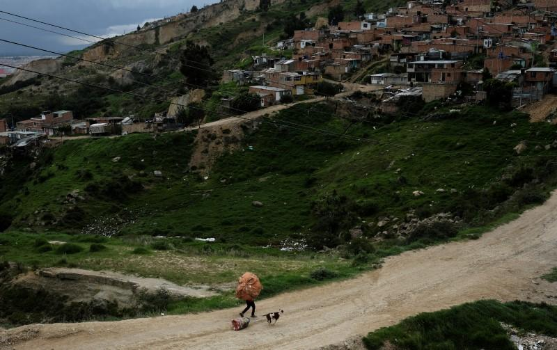 A man carries recycled material next to his dog, pulling a bag with recycled material with its mouth, in a slum in Soacha