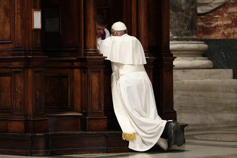 Pope Francis kneels before a priest to confess during the Liturgy of Penance on March 17, 2017 in St. Peter's Basilica at the Vatican