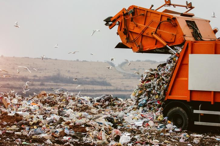 A garbage truck unloading at a landfill.
