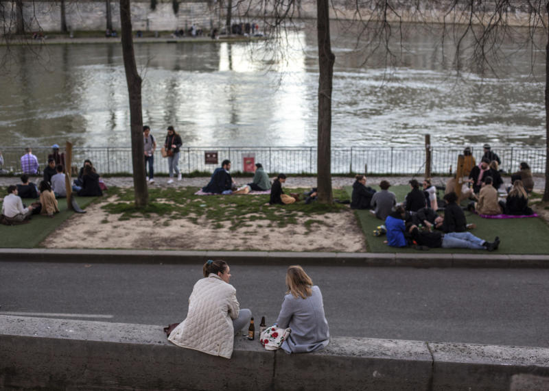 People stroll along the Seine river banks at sunset Sunday March 15, 2020 in Paris. (AP Photo/Rafael Yaghobzadeh)