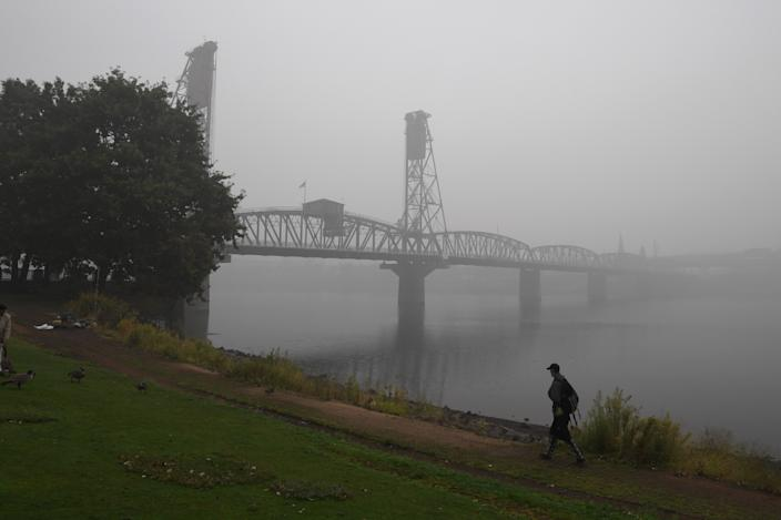 A man walks along the banks of the Williamette River in downtown Portland, Oregon, on September 14, 2020.