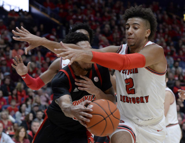 Louisville guard Lamarr Kimble, left, passes the ball around Western Kentucky guard Jared Savage (2) during the second half of an NCAA college basketball game Friday, Nov. 29, 2019, in Nashville, Tenn. (AP Photo/Mark Zaleski)