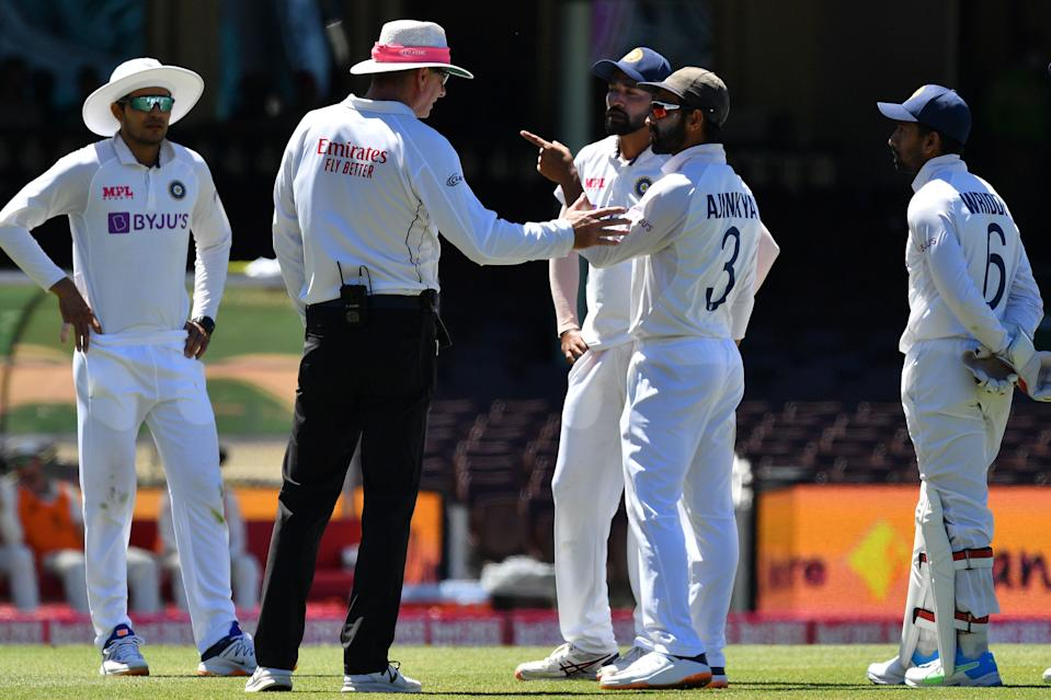 India's captain Ajinkya Rahane (2R) and his teammate Mohammed Siraj (3R) speak to the umpire as the game was halted after allegedly some remarks were made by the spectators on the fourth day of the third cricket Test match between Australia and India at the Sydney Cricket Ground (SCG) in Sydney on January 10, 2021. (Photo by SAEED KHAN/AFP via Getty Images)